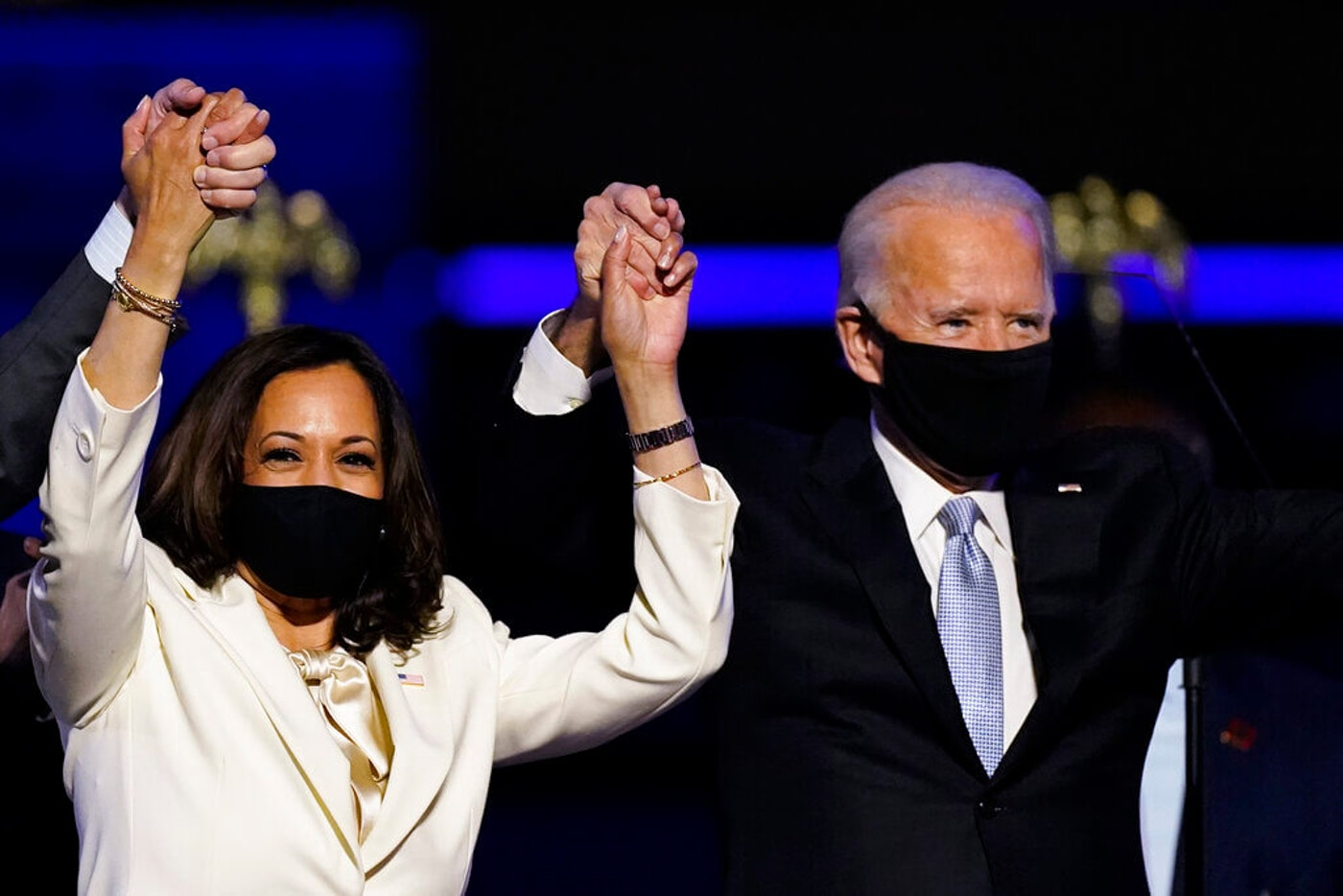 In this Nov. 7, 2020, file photo Vice President-elect Kamala Harris holds hands with President-elect Joe Biden and her husband Doug Emhoff as they celebrate in Wilmington, Del. (AP Photo/Andrew Harnik, File)