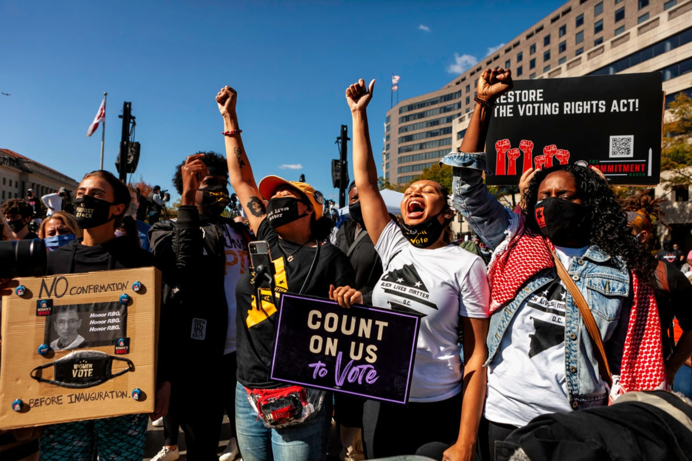 Washington Black Lives Matter activists raise their fists and cheer a colleague who is speaking to the Women's March on Oct. 17, 2020. Image via Shutterstock.