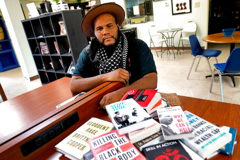 Black-owned bookstore owner Ali Nervis displaying anti-racist books in his store