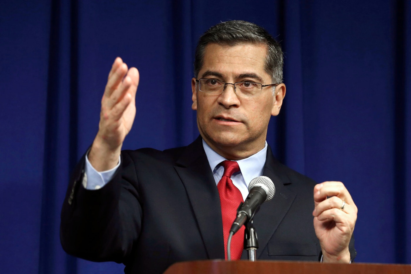 Attorney general Xavier Becerra standing at microphone speaking and gesturing with hand