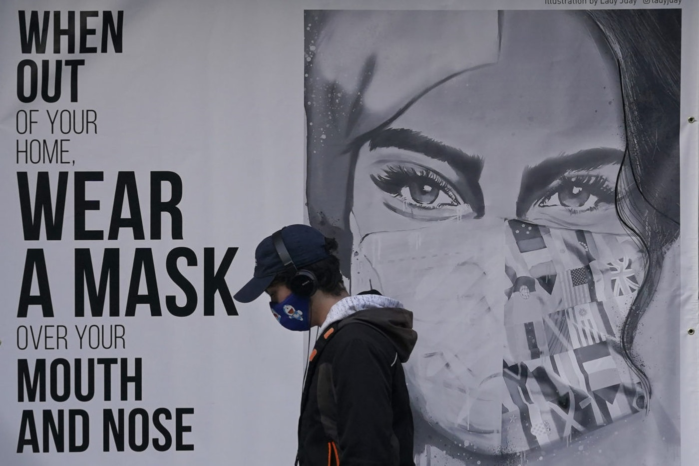 """A pedestrian walks past a mural reading: """"When out of your home, Wear a mask over your mouth and nose,"""" during the coronavirus outbreak in San Francisco. (AP Photo/Jeff Chiu, File)"""
