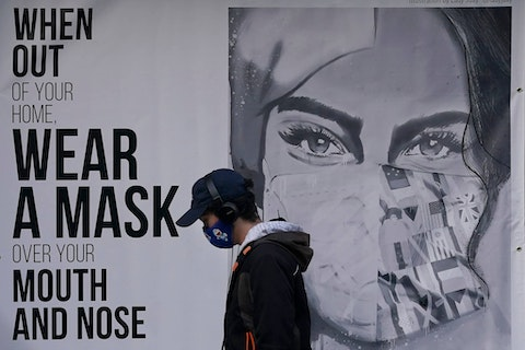 "A pedestrian walks past a mural reading: ""When out of your home, Wear a mask over your mouth and nose,"" during the coronavirus outbreak in San Francisco. (AP Photo/Jeff Chiu, File)"