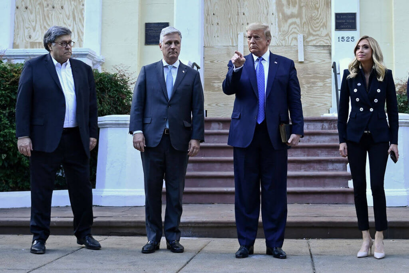 US President Donald Trump holds up a Bible as he gestures, alongside US Attorney General William Barr (L), White House national security adviser Robert O'Brien (2nd-L) and White House press secretary Kayleigh McEnany, outside of St John's Episcopal church across Lafayette Park in Washington, DC on June 1, 2020. (Photo by BRENDAN SMIALOWSKI/AFP via Getty Images)