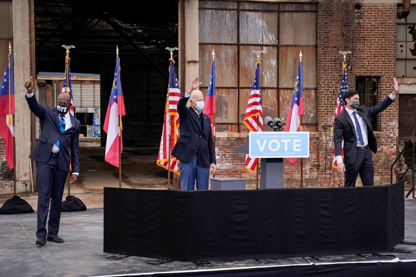 ATLANTA, GA - DECEMBER 15: Flanked by U.S. Democratic Senate candidates Rev. Raphael Warnock (L) and Jon Ossoff (R), U.S. President-elect Joe Biden gestures to the crowd at the end of a drive-in rally at Pullman Yard on December 15, 2020 in Atlanta, Georgia. (Photo by Drew Angerer/Getty Images)