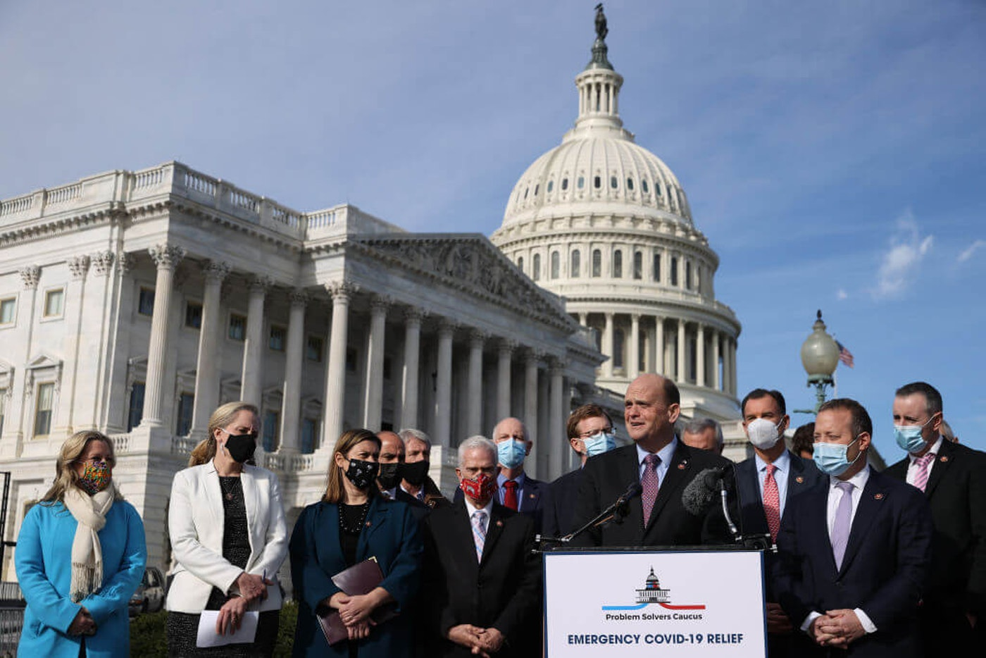 WASHINGTON, DC - DECEMBER 03:  Rep. Tom Reed (R-NY) (at lectern) and Rep. Josh Gottheimer (D-NJ) (2nd R), co-chairs of the bipartisan Problem Solvers Caucus, hold a news conference with fellow members of Congress to highlight the need for bipartisan, bicameral COVID-19 relief legislation outside the U.S. Capitol on December 03, 2020 in Washington, DC. With the holiday season approaching and the legislative session coming to a close, federal government funding for critical coronavirus relief programs is set to expire as the U.S. faces daily records for infections, hospitalizations, and deaths. (Photo by Chip Somodevilla/Getty Images)