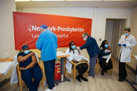Doctors inject sisters Claudia Scott-Mighty, left, Althea Scott-Bonaparte, who are patient care directors, and Christine Scott, an ICU nurse, with their second shot of the Pfizer vaccine at NewYork-Presbyterian Lawrence Hospital on Friday, Jan. 8, 2021. (AP Photo/Kevin Hagen).