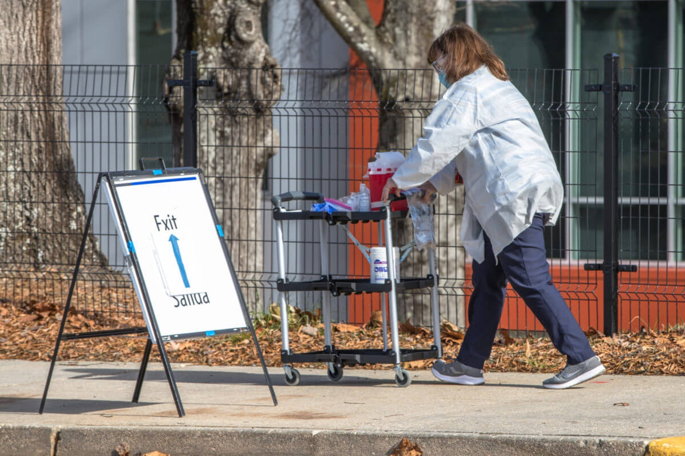 A medical professional heads to the parking lot  at BoJangles Arena  in Charlotte to administer the Covid-19 vaccine to a patient in their vehicle. Photo by Grant Baldwin for Courier Newsroom.