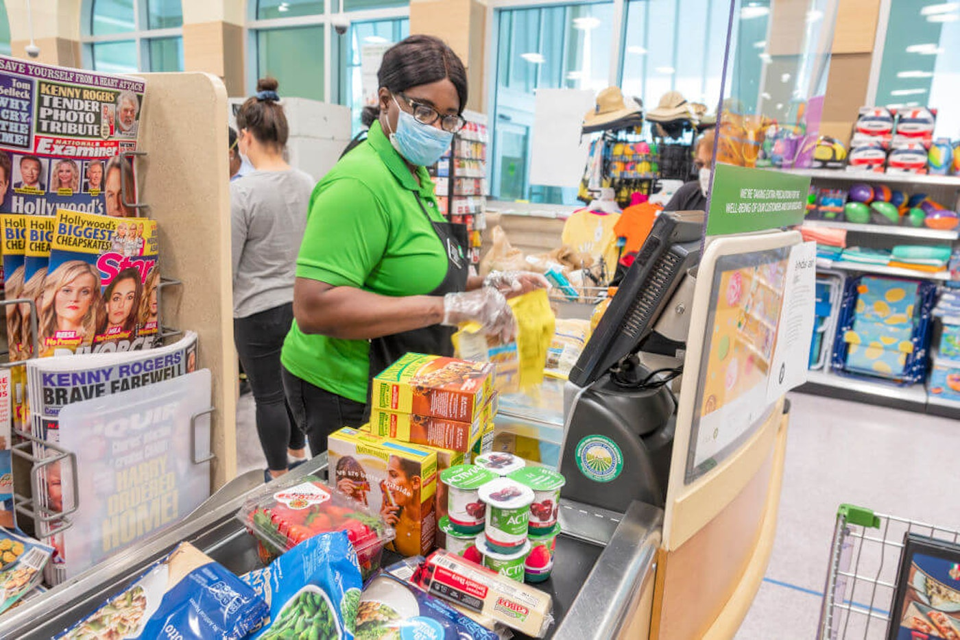 Black woman working at grocery store; Black and Latina women hit hard by job loss