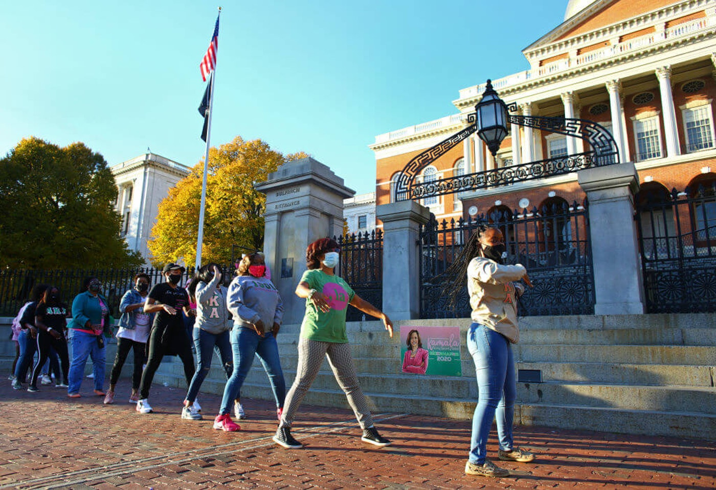 The group dances in a marching circle, called the AKA International Stroll.  Members of different chapters of the Alpha Kappa Alpha sorority gather in front of the Massachusetts State House to celebrate Vice President-elect Kamala Harris (Pat Greenhouse/Globe Staff)