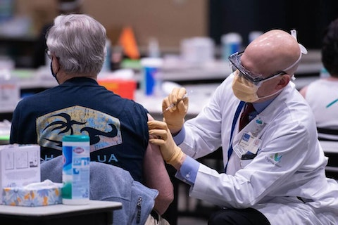 Chief clinical officer John Corman MD at Virginia Mason administers a dose of the Pfizer Covid-19 vaccine at the Amazon Meeting Center in downtown Seattle, Washington on January 24, 2021. - (Photo by GRANT HINDSLEY/AFP via Getty Images)