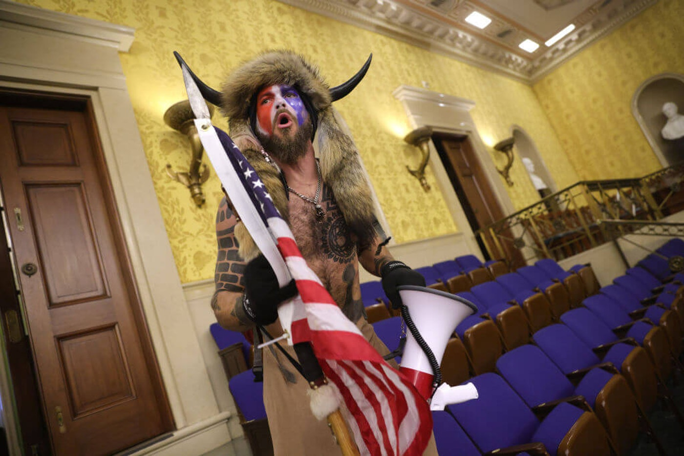 """A protester screams """"Freedom"""" inside the Senate chamber after the U.S. Capitol was breached by a mob during a joint session of Congress on January 06, 2021 in Washington, DC. (Photo by Win McNamee/Getty Images)"""