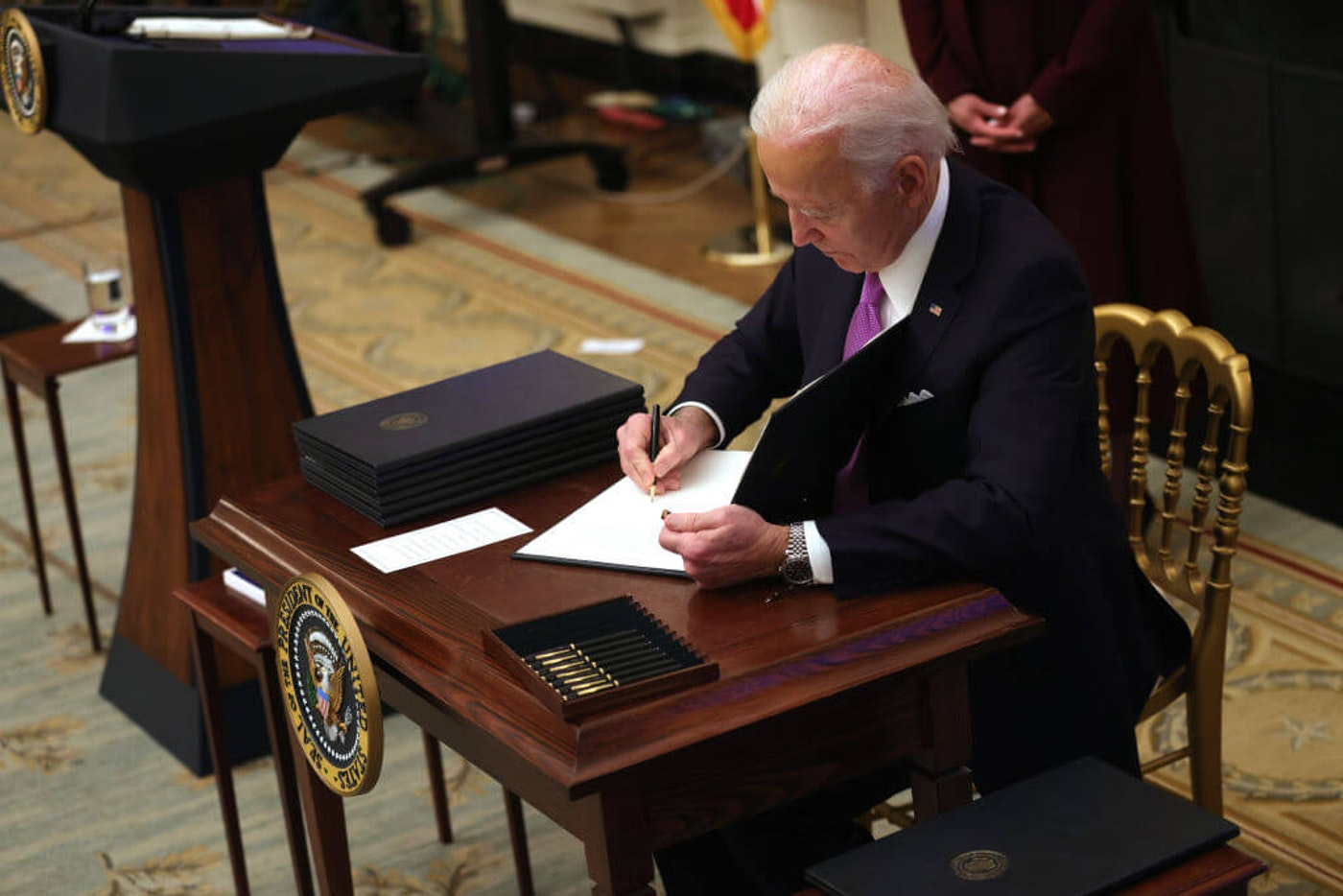 U.S. President Joe Biden signs an executive order during an event in the State Dining Room of the White House January 21, 2021 in Washington, DC. President Biden delivered remarks on his administration's COVID-19 response, and signed executive orders and other presidential actions. (Photo by Alex Wong/Getty Images)