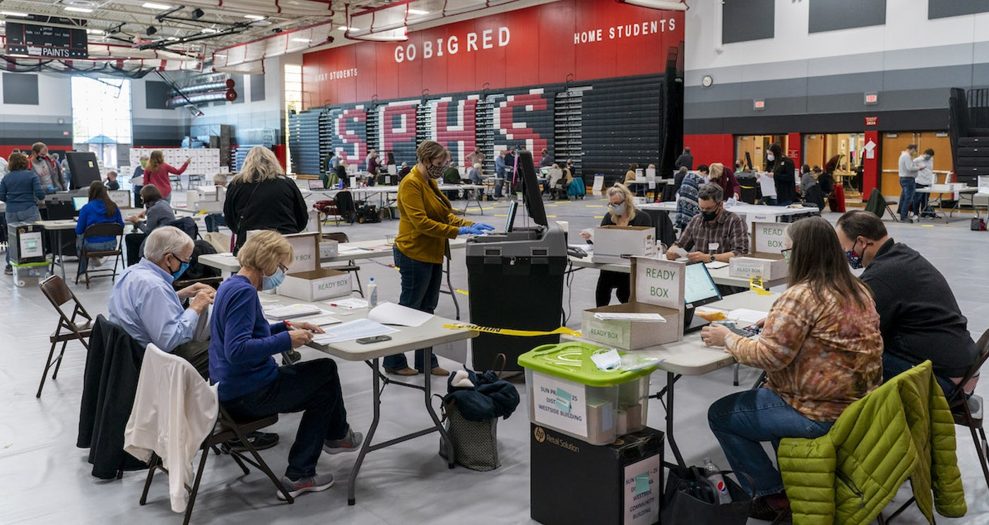 Poll worker Rebecca Brandt, center, feeds a voting tabulation machine with absentee ballots in the gym at Sun Prairie High School on Nov. 3 in Sun Prairie. The entire gym was dedicated to counting the absentee ballots. (Photo by Andy Manis/Getty Images)