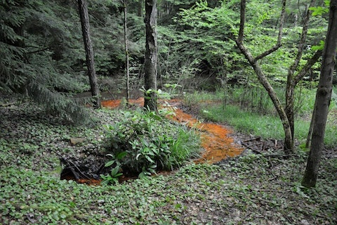 An acid mine drainage well was located on the bank of a tributary to Montgomery Creek. DEP successfully plugged the abandoned well. (PA Department of Environmental Protection)