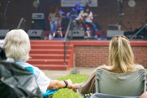 """Joyce Massucci, right, holds hands with her friend """"Smiling Dave"""" as they listen to """"Soulful Femme"""" on the first day of the Franklin Blues & Barbecue Festival, Saturday, June 19, in Franklin, Pa. The annual festival with free music, returned after being canceled last year due to COVID-19, uses proceeds from vendors and sponsors to support the music programs in the local public schools. The festival helped celebrate the first Juneteenth celebration in the city.(AP Photo/Keith Srakocic)"""