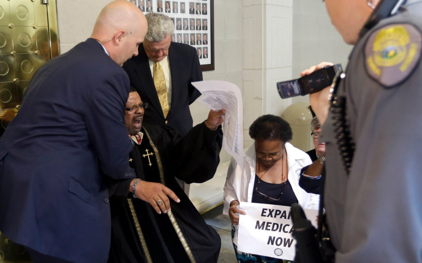 Reverend Gregory Hardy is arrested in April 2015 as he and other clergy members demonstrate for Medicaid expansion outside the Senate chamber at the North Carolina Legislature in Raleigh, N.C. (AP Photo/Gerry Broome)