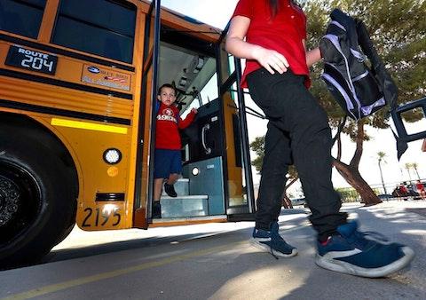 two children walking off a school bus