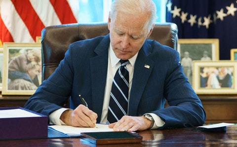 President Joe Biden signs the American Rescue Plan on March 11, 2021, in the Oval Office of the White House in Washington, DC. (Photo by MANDEL NGAN/AFP via Getty Images)