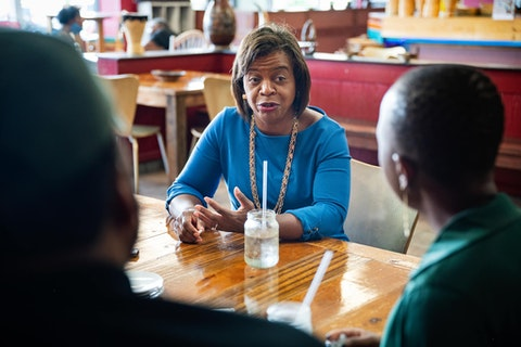 Cheri Beasley sits at a table in a restaurant with potential supporters in Durham, NC.