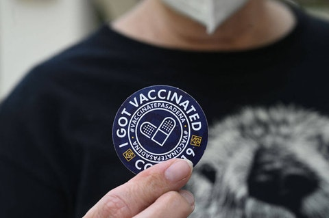 """A woman holds up a sticker after getting her third """"booster"""" dose of Covid-19 vaccine at a clinic. (Photo by ROBYN BECK/AFP via Getty Images)"""