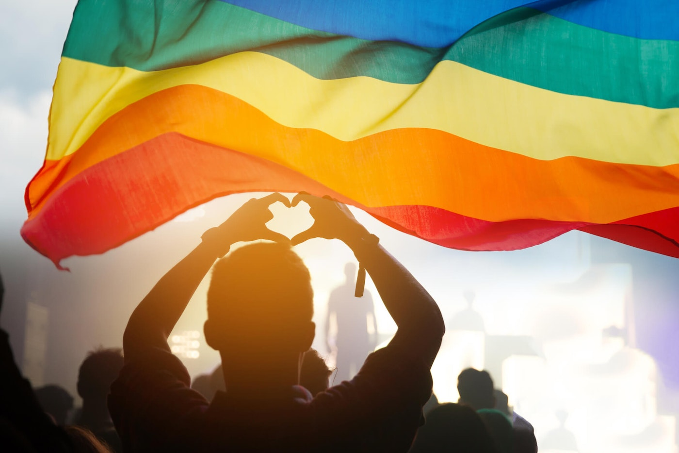 A person backlit by the sun makes a shape of a heart with their fingers while standing beneath a rainbow flag.
