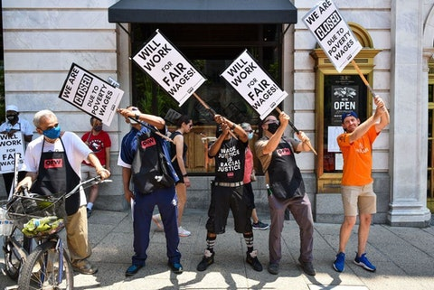 Activists take part in a protest outside of the Old Ebbitt Grill to call for a full minimum wage with tips for restaurant workers in Washington, DC in May 2021. (Photo by MANDEL NGAN / AFP via Getty Images)