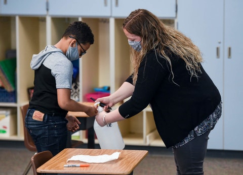 Learning support teacher Sabrina Werley holds the bottle of hand sanitizer for a student at Cumru Elementary School in Berks County. (Reading Eagle Photo via Getty Images/ Ben Hasty)