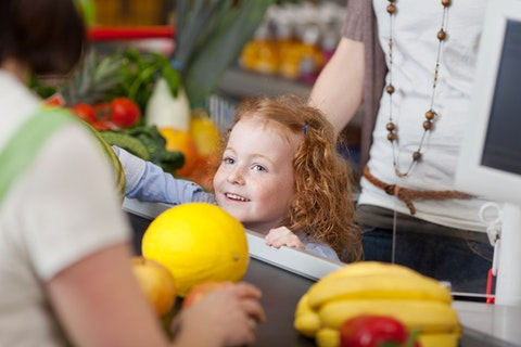 little girl smiling at cashier at grocery store checkout