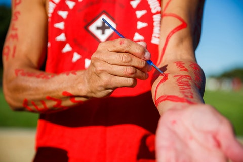 person painting words on their arm with red paint