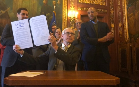 Gov. Tony Evers signs an executive order on Jan. 27 authorizing the creation of a nonpartisan commission to draw fair maps for the next redistricting process. Members of the commission met for the first time Thursday. (Photo by Jessica VanEgeren)