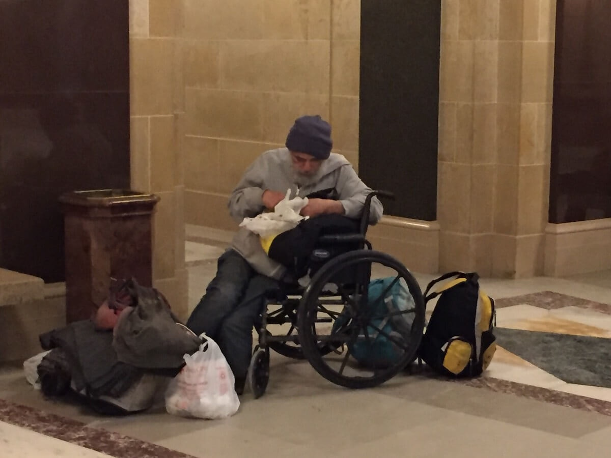 A homeless man seeks shelter from the cold in the rotunda of the state Capitol building on Jan. 21. (Photo by Julian Emerson)