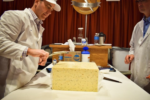 Matt Lambric, a Baraboo cheesemaker and pepper-flavored high-heat cheese judge for the World Championship Cheese Contest in Madison, pulls a sample from a block. (Photo by Jonathon Sadowski)