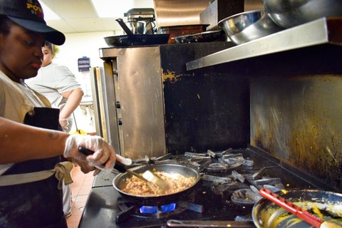 Shania Hutchins, kitchen manager at The Tandem in Milwaukee, cooks Thursday afternoon. The restaurant is giving away free, high-quality community meals to help during the coronavirus outbreak. (Photo by Jonathon Sadowski)