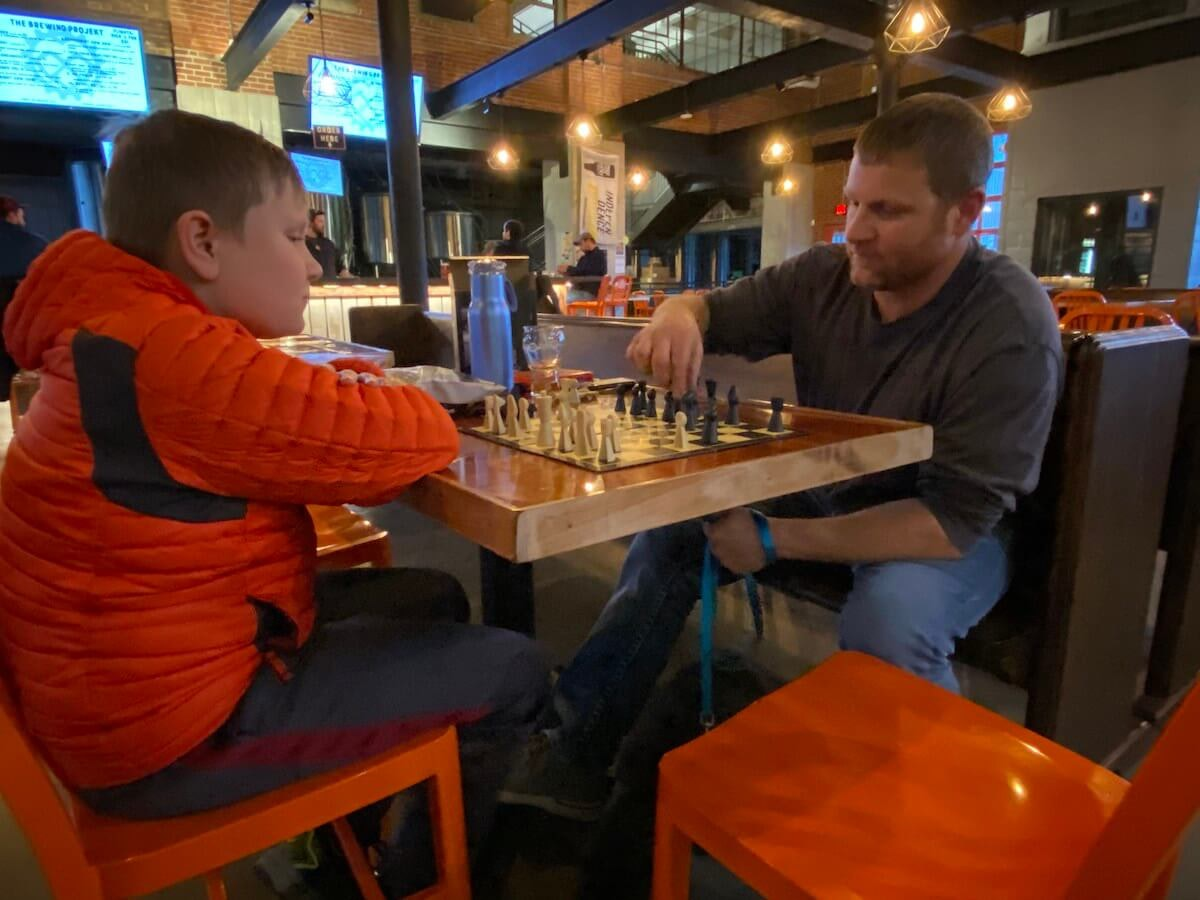Dave Weiss plays chess with his 11-year-old son Dalton Thursday at The Brewing Projekt in Eau Claire. Brewing Projekt owner William Glass said he believes coronavirus concerns will hinder business at his establishment and others across Wisconsin. (Photo by Julian Emerson)