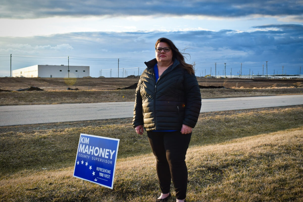 Kim Mahoney stands near a campaign sign in her yard in Mount Pleasant. In the distance is the sprawling Foxconn Technology Group development. Mahoney narrowly lost her race for the Racine County Board, falling just 62 votes short. (Photo by Jonathon Sadowski)