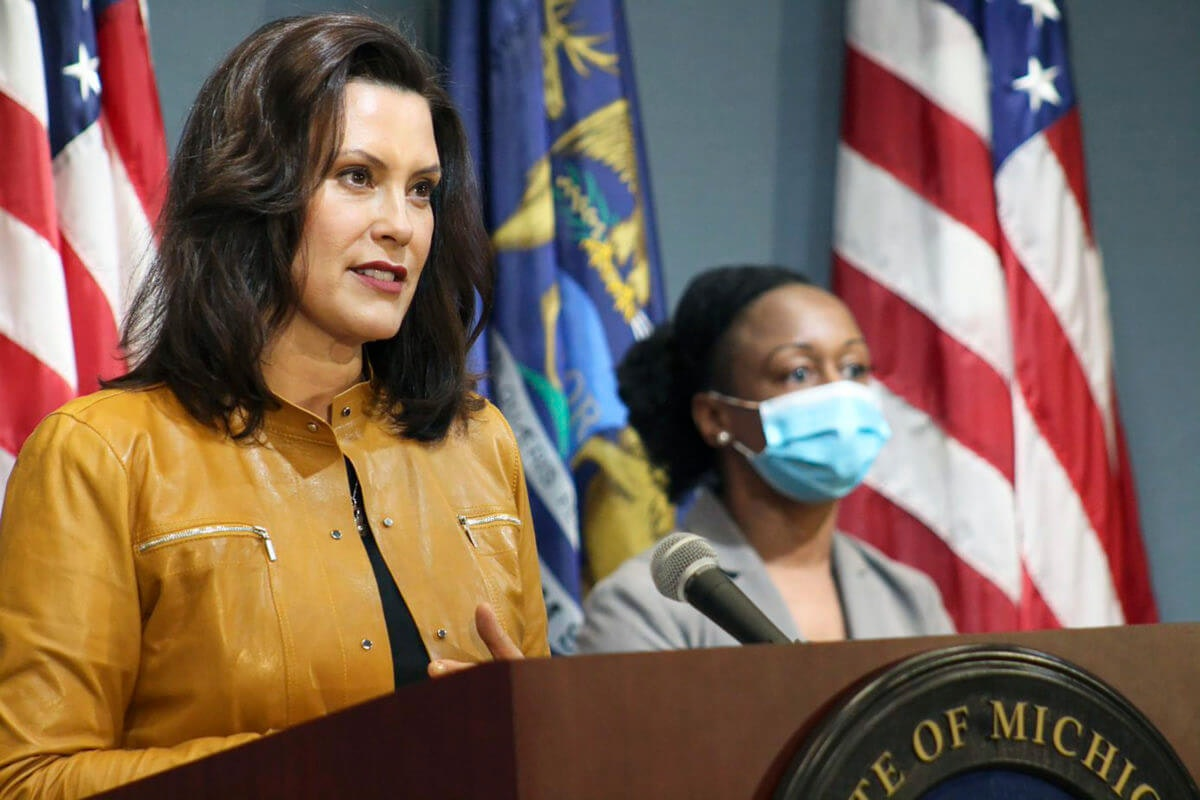 Flag-waving, honking protesters drove past the Michigan Capitol on Wednesday to show their displeasure with Gov. Gretchen Whitmer's orders to keep people at home and businesses locked during the new coronavirus COVID-19 outbreak. (AP Photo/Paul Sancya)