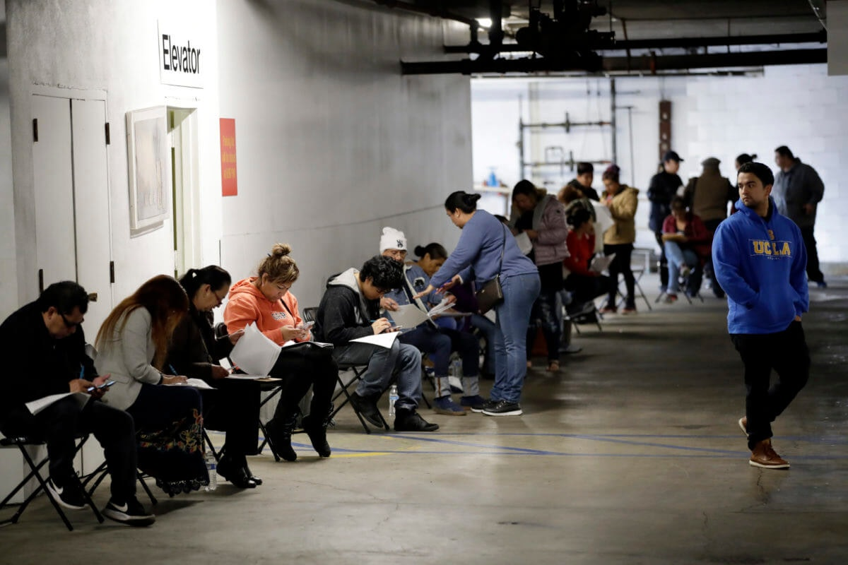 Hospitality workers wait in line in a basement garage to apply for unemployment benefits