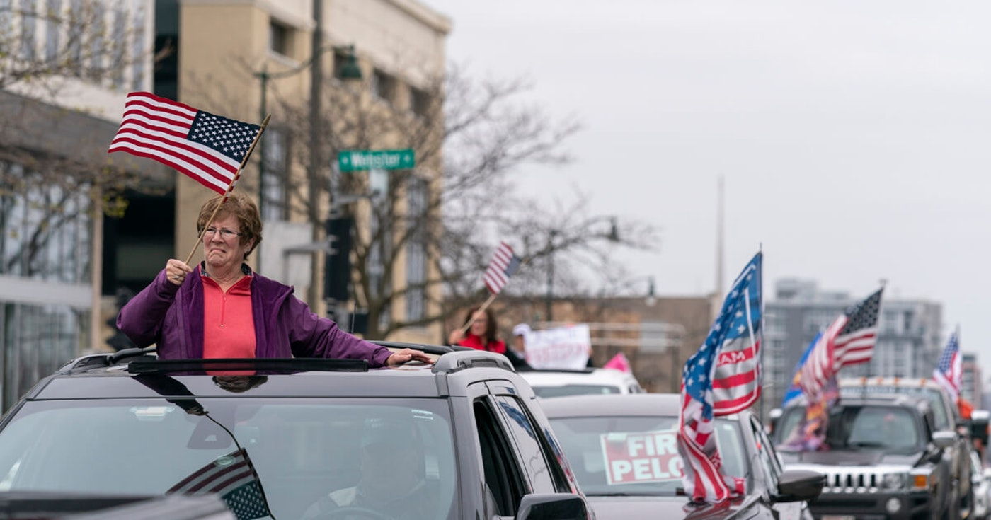 Women wave the American flag as vehicles circle the State Capitol Friday in Madison.