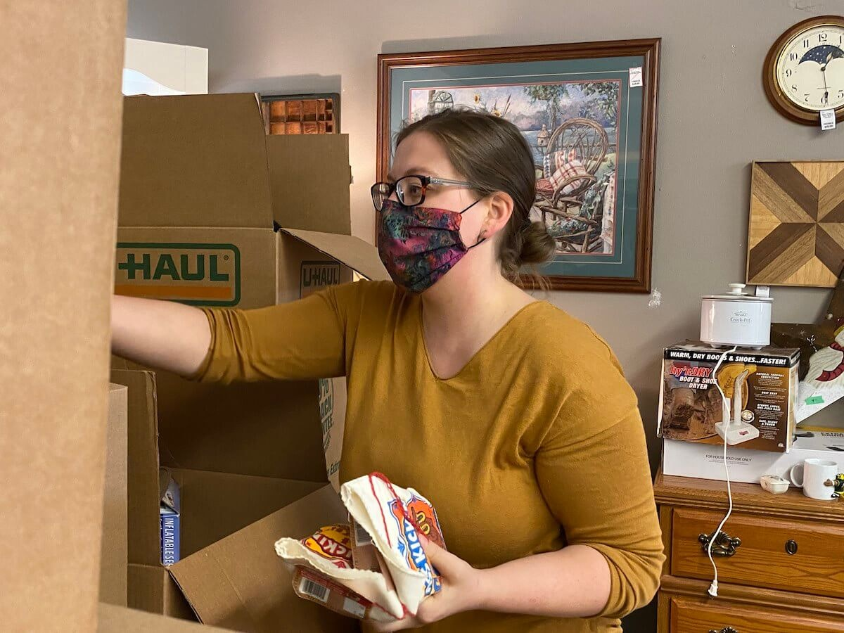 Megan Glassbrenner unpacks boxes from a recent estate sale. She plans to sell the items at The Attic Home Consignments & Estate Sales store in Eau Claire that she owns with her husband, John. John said he was relieved to receive paycheck protection funding totaling $8,500 on Friday to help keep their Eau Claire business financially viable. (Photo by Julian Emerson)