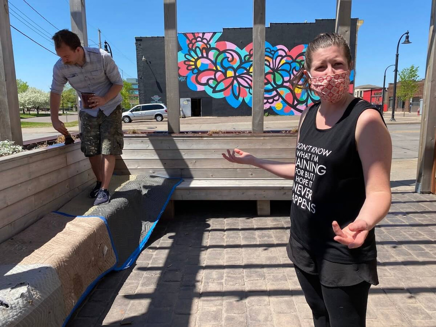 Kayla Midthun, who owns Ramone's Ice Cream Parlor in downtown Eau Claire with her husband Blayne, discusses efforts they have taken to protect customers and employees from COVID-19 as Blayne applies stain to a deck outside the shop Wednesday.