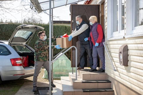 Public support for quarantine safeguards is helped by volunteers delivering goods to those staying safer at home. (Shutterstock image)