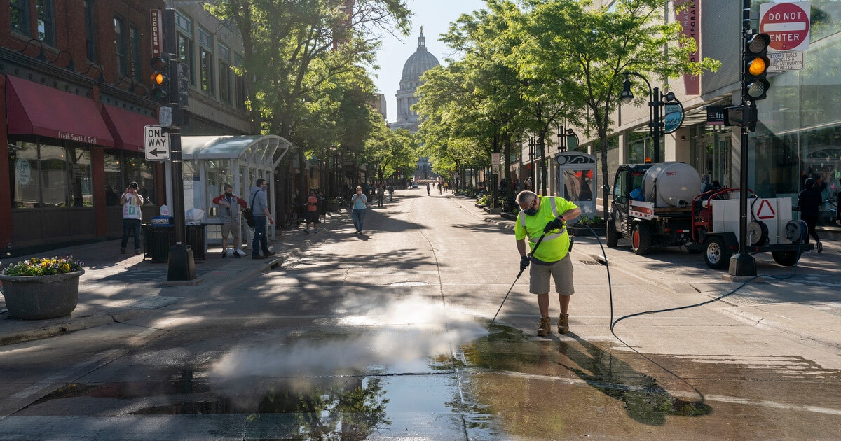 Peter Castro with the city of Madison parks department cleans up State Street after Saturday protests.
