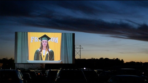 Caps and Gowns and a Great Big Screen as a Wisconsin Class Graduates at a Drive-In