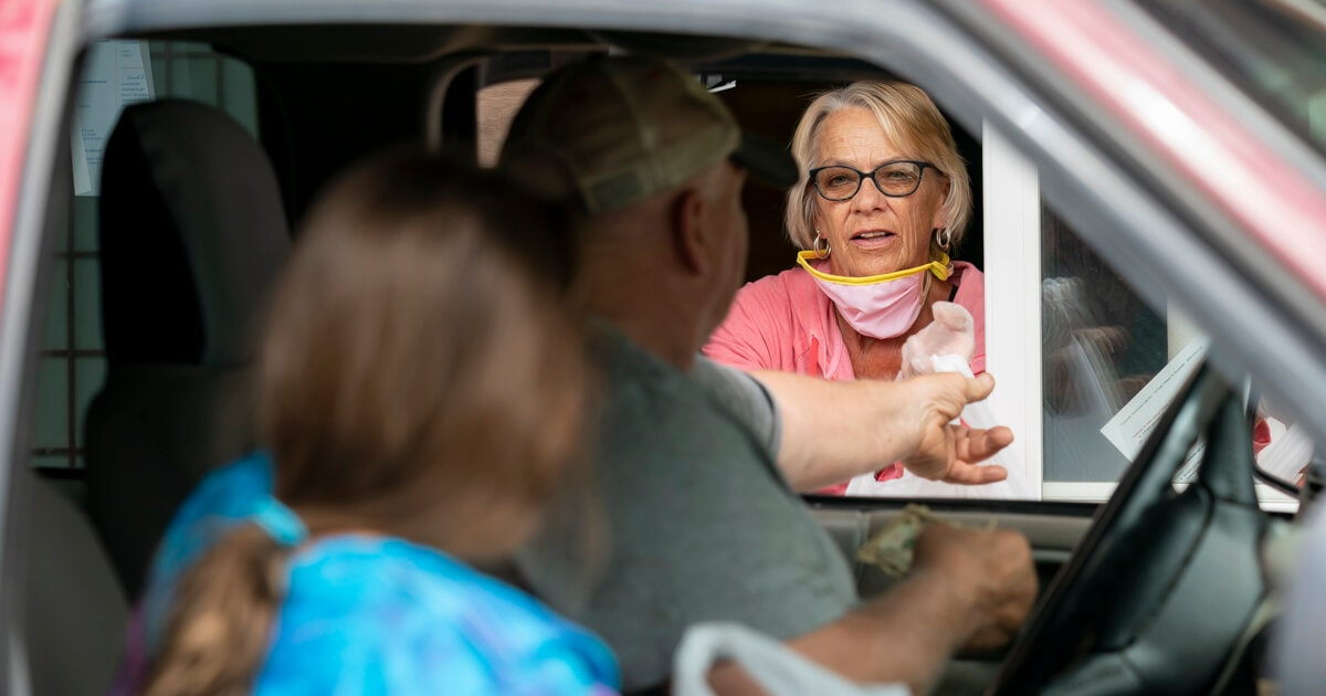 Volunteer Lana Dyreson hands out food to customers at the the Barneveld Community Café in Barneveld. The owners of the restaurant eliminated prices on the menu so those struggling with unemployment and unable to make ends meet can still get a warm meal. (Photo © Andy Manis)