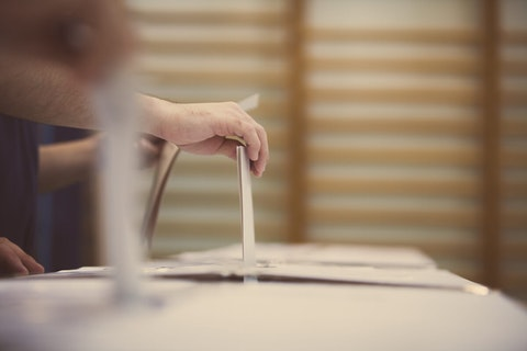 Ballot being dropped into a collection box. (Shutterstock image)