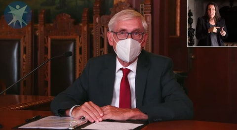 Gov. Tony Evers wears a mask while discussing rising COVID-19 numbers in Wisconsin