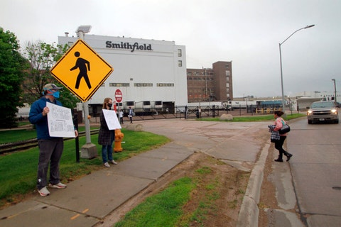 In this May 20, 2020 file photo, residents held thank you signs to greet employees of a Smithfield pork processing plant as they returned to their shifts after the plant had been closed because of a coronavirus outbreak in Sioux Falls, S.D. (AP Photo/Stephen Groves File)