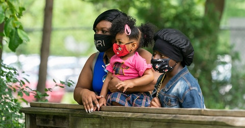 Khayriyyah Khaaliq stands with her daughters Ashyra Khaaliq, 2, and 7th-grader Jakyra Johnson, at Henry Vilas Zoo in July shortly after the mandatory mask ordinance took effect in Dane County. (Photo @ Andy Manis)