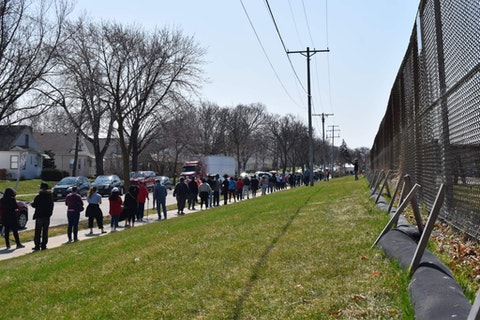 Voters wait in long lines outside one of Milwaukee's five polling places on Apr. 7, 2020.