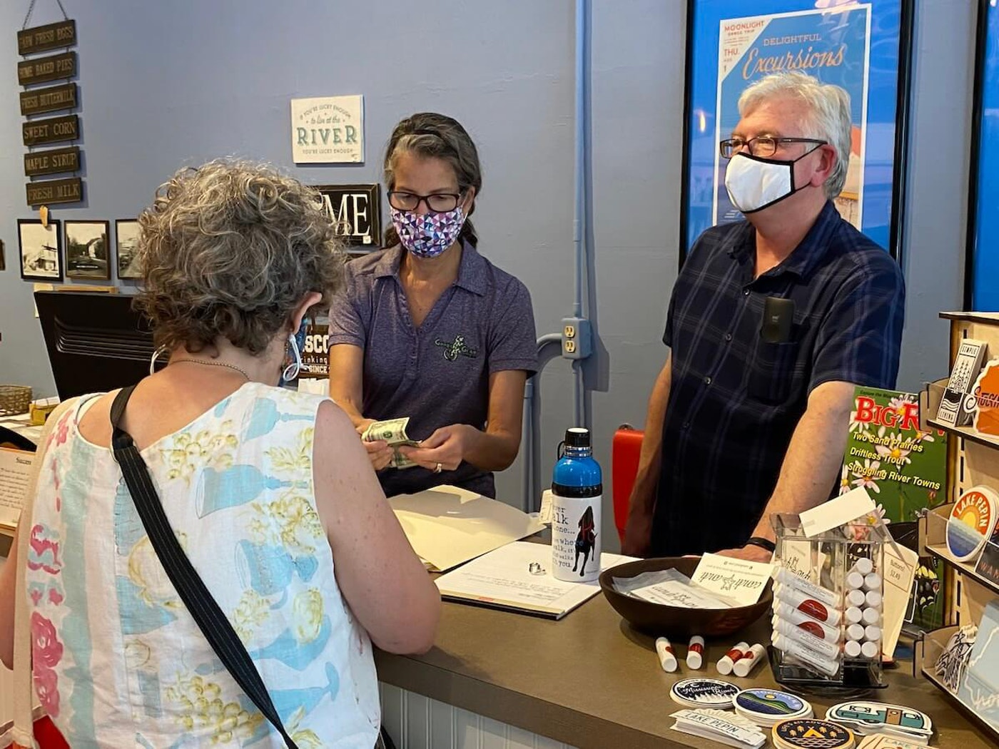 Alan Nugent, right, owner of the Stockholm Pie and General Store, works with a fellow employee and a customer on Aug. 1, the first day of Gov. Tony Evers' order making the wearing of masks in public places in Wisconsin mandatory. Nugent said a handful of people have left his store because they would not wear masks, but most people abide by the regulation. (Photo by Julian Emerson)